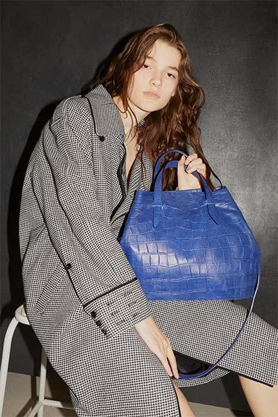 portrait d'une femme assise portant un sac bleu Lilu